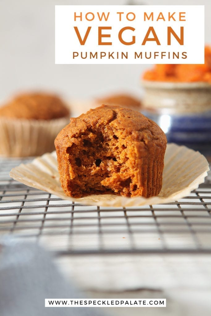 An orange muffin with a bite taken out of it on a wire rack with the text 'how to make vegan pumpkin muffins'