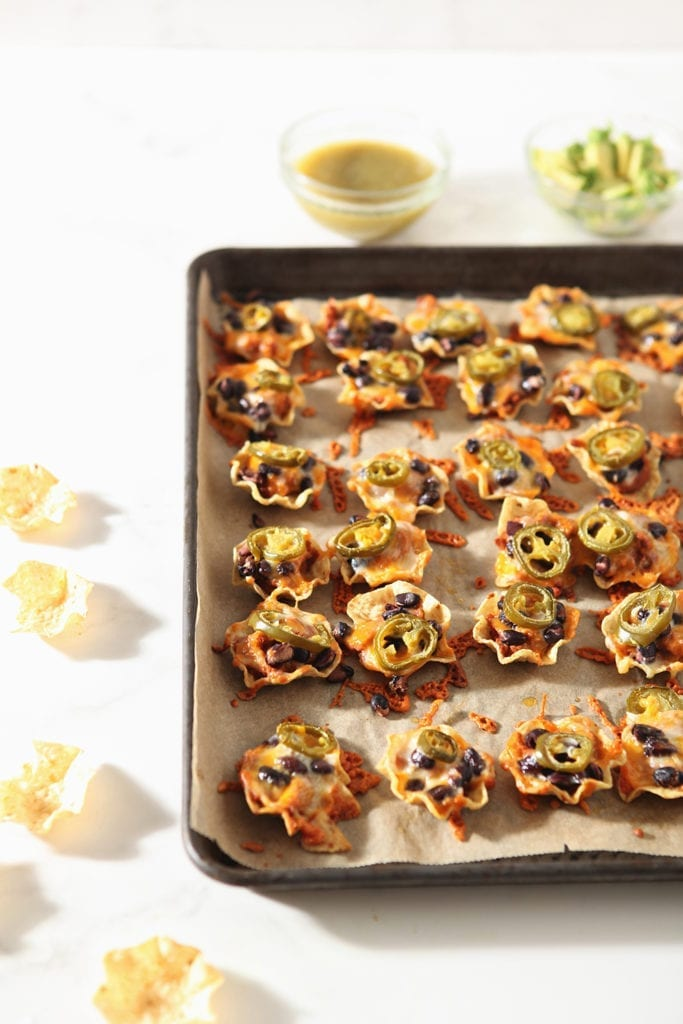 Taco cups are shown on a baking sheet after baking, before toppings are added.