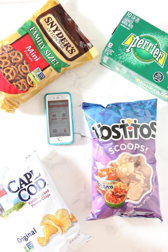 Bags of chips surround a phone, which shows the Tom Thumb app