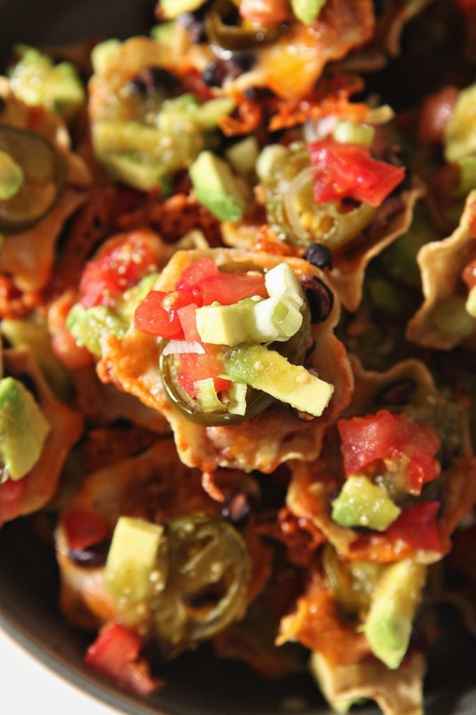 The garnished individual loaded nachos are shown from above, close up