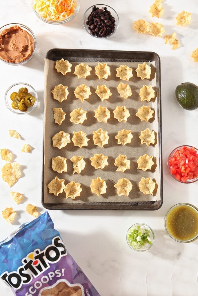 Tortilla chips are laid out on a baking sheet before being filled with nacho ingredients