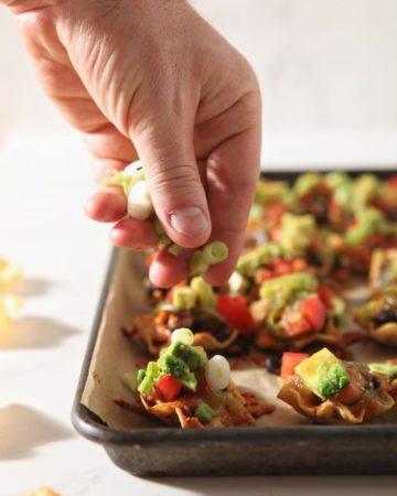 green onions are sprinkled on top of baked taco cups before serving