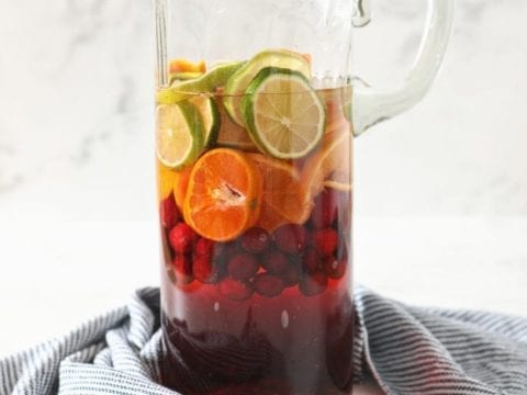A pitcher holds oranges, limes, cranberries and ingredients for sangria