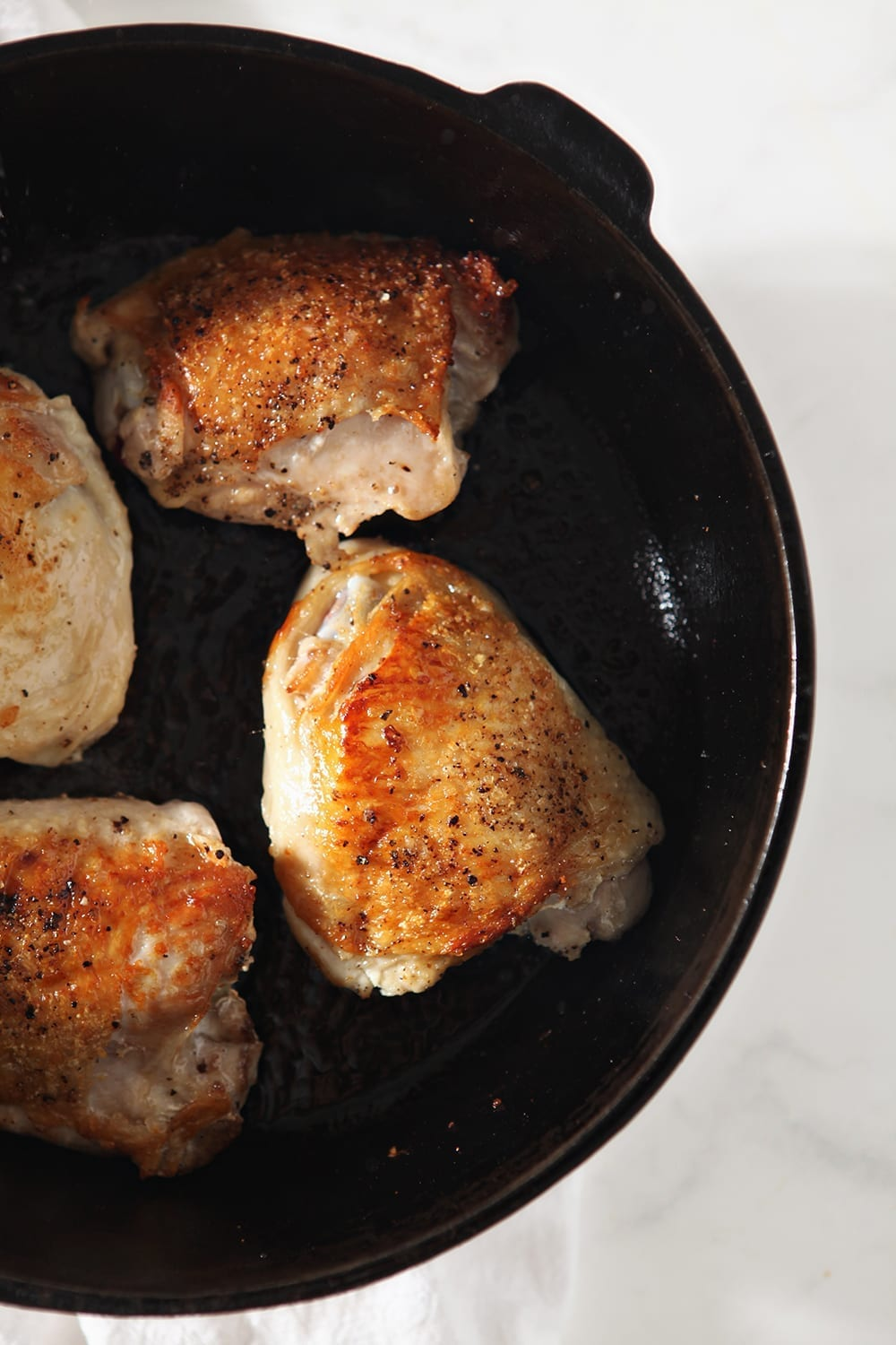 Seared bone-in, skin-on chicken thighs, in a cast iron skillet
