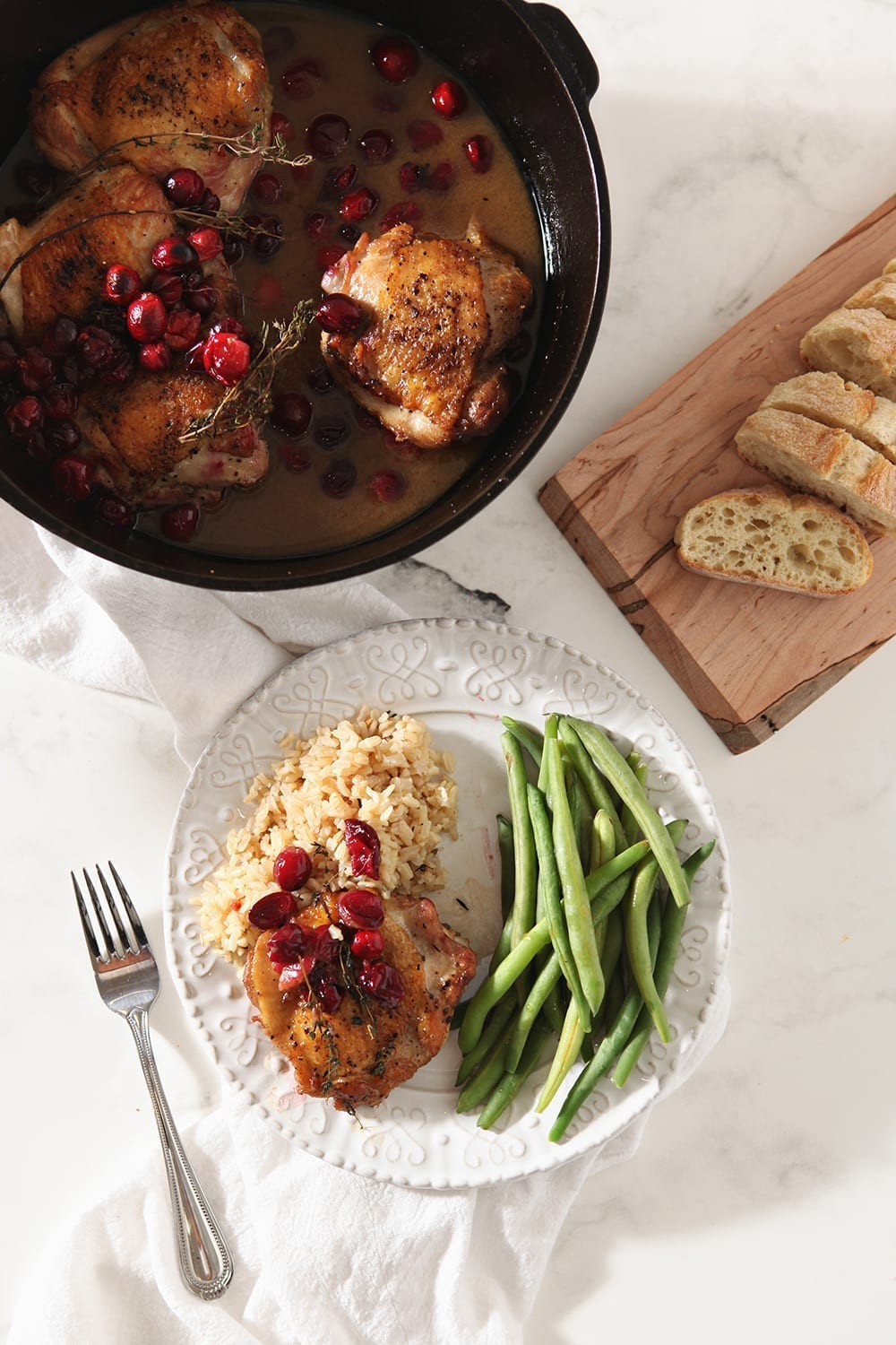Overhead image of a cranberry chicken thigh on a plate, with rice and steamed green beans