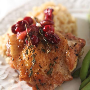 Close up of a Cranberry Chicken Thigh with brown rice and green beans on a plate
