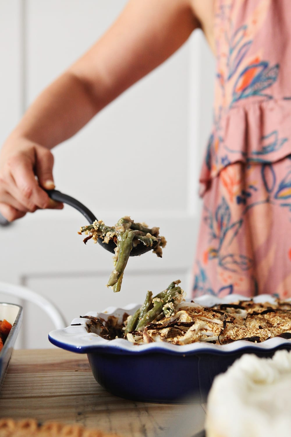 A woman lifts a spoon of Fresh Green Bean Casserole out of the dish