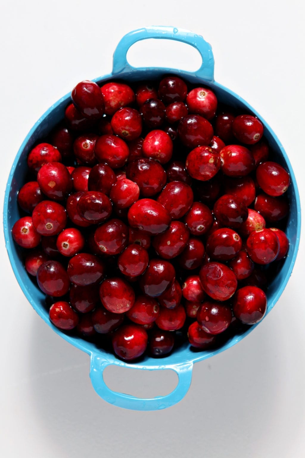 Cranberries sit in a blue colander, from above