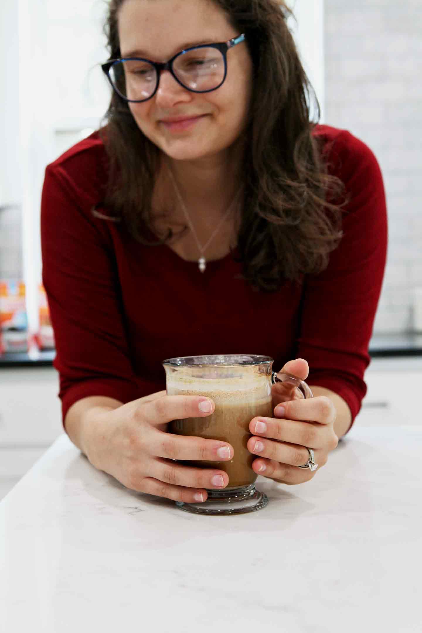 A woman holds a mug of coffee