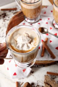 A person holds a mug of coffee with Gingerbread Coffee Creamer and Spiced Whipped Cream, above other mugs of the same
