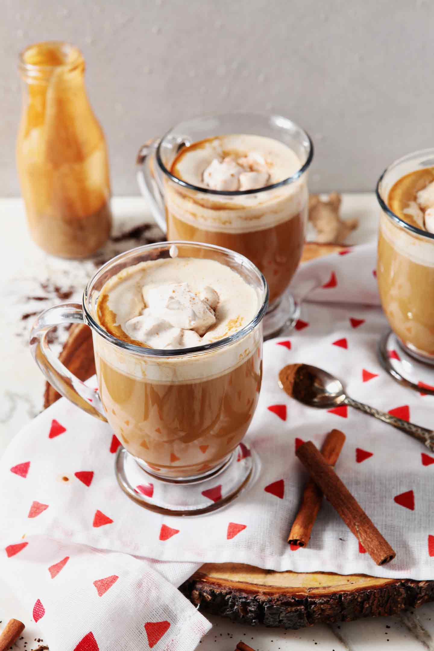 Three mugs of coffee with Homemade Gingerbread Coffee Creamer and spiced whipped cream sit on a marble surface, before drinking