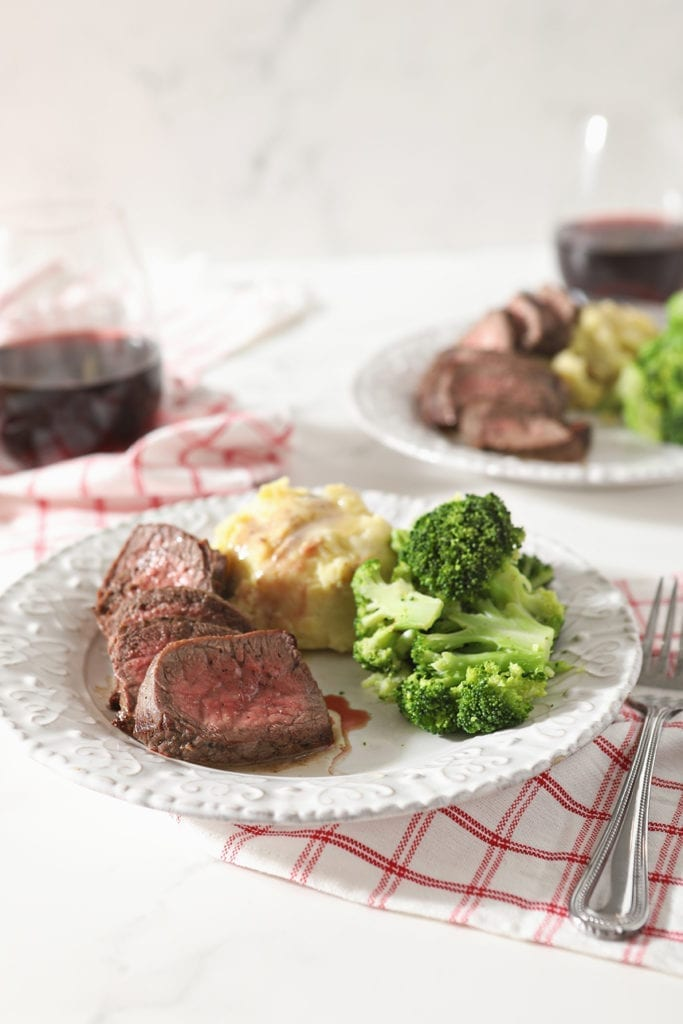 Sliced top sirloin steak on a white plate with broccoli and mashed potatoes, with wine