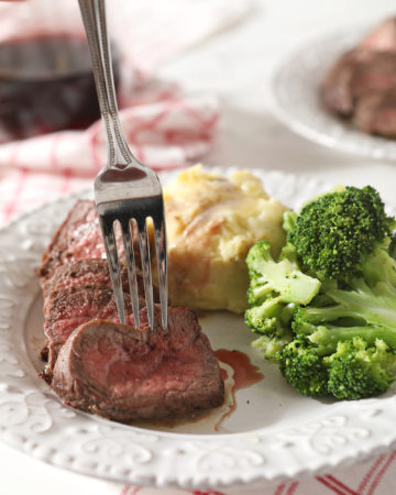 A fork sticks a sliced piece of steak before lifting it from the plate