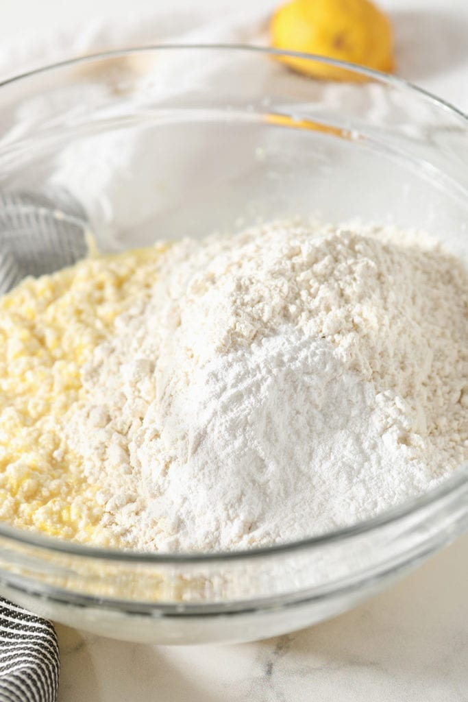 Dry ingredients sit on top of wet ingredients in a clear bowl, before blending