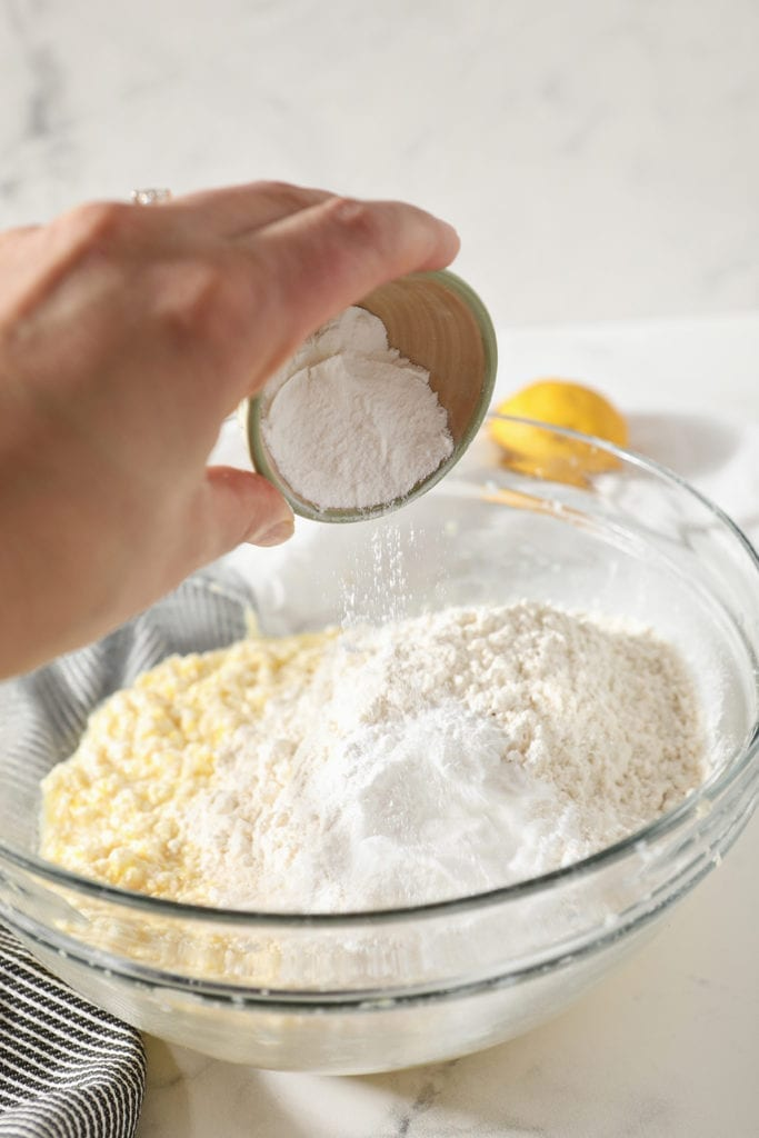 Baking powder is sprinkled into a bowl containing cookie dough, before mixing