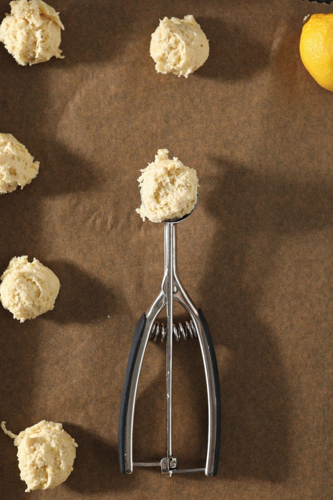 A cookie scoop holds a portion of lemon drop cookie batter on a baking sheet next to scooped cookies