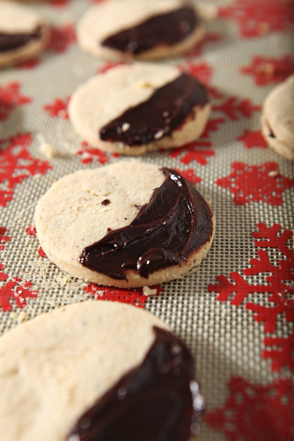 Shortbread cookies, slathered with a ganache, sit on a baking sheet