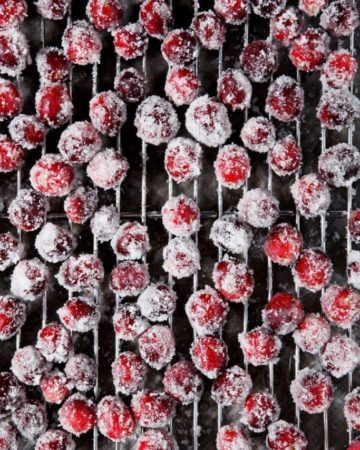 Sugared cranberries sit on a cooling rack, after chilling in the fridge