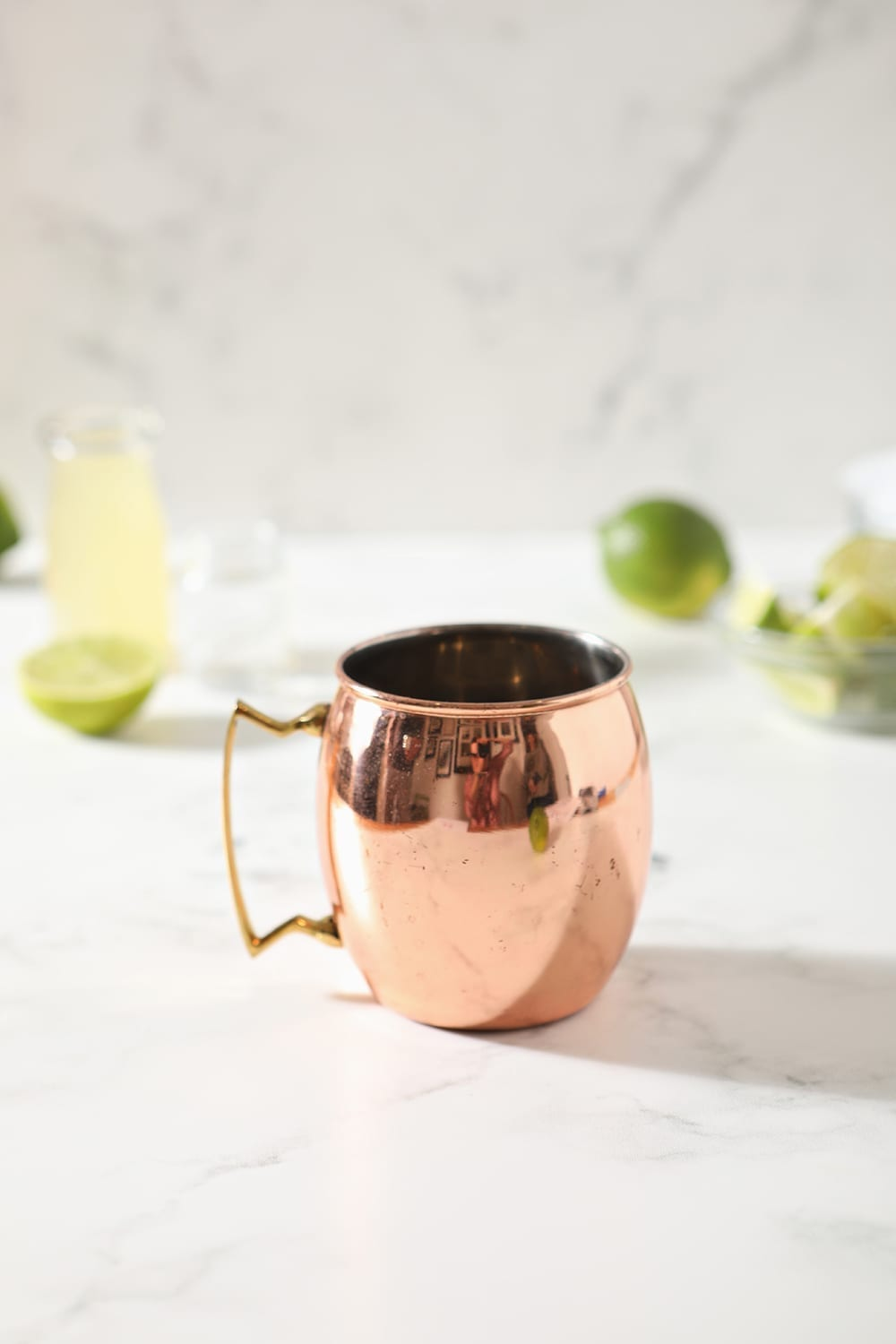 A copper mug sits on a marble countertop with drink ingredients scattered around it