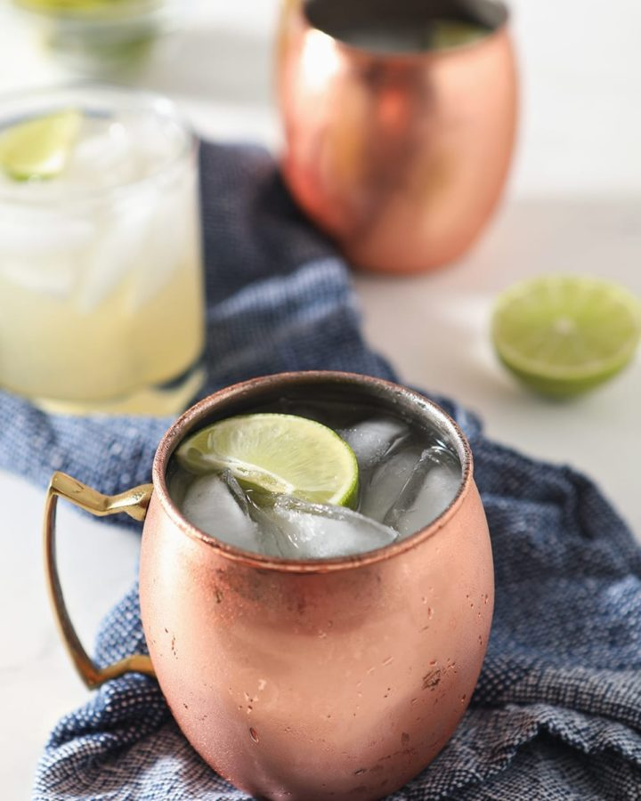 Close up of a copper mug holding a Moscow Mule, garnished with a lime, on a blue towel