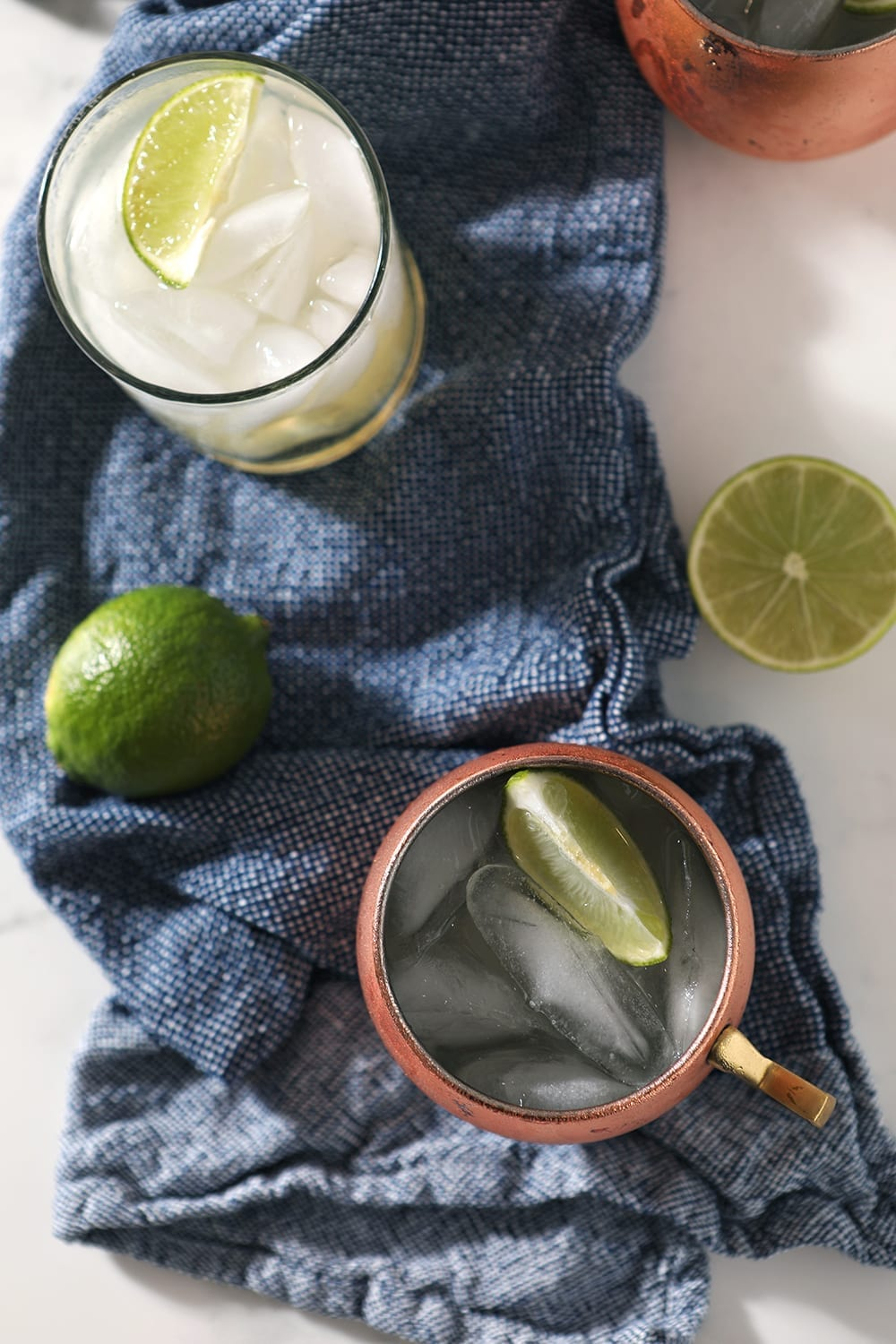 Overhead of three drinks on a blue towel, with limes scattered around them