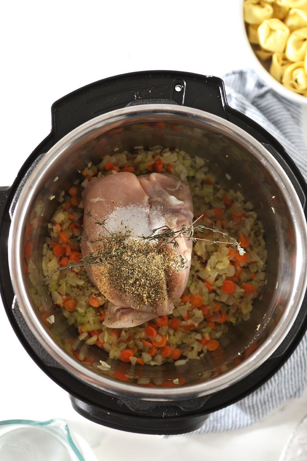 Chicken, veggies and seasonings are laid in the INstant Pot, before cooking