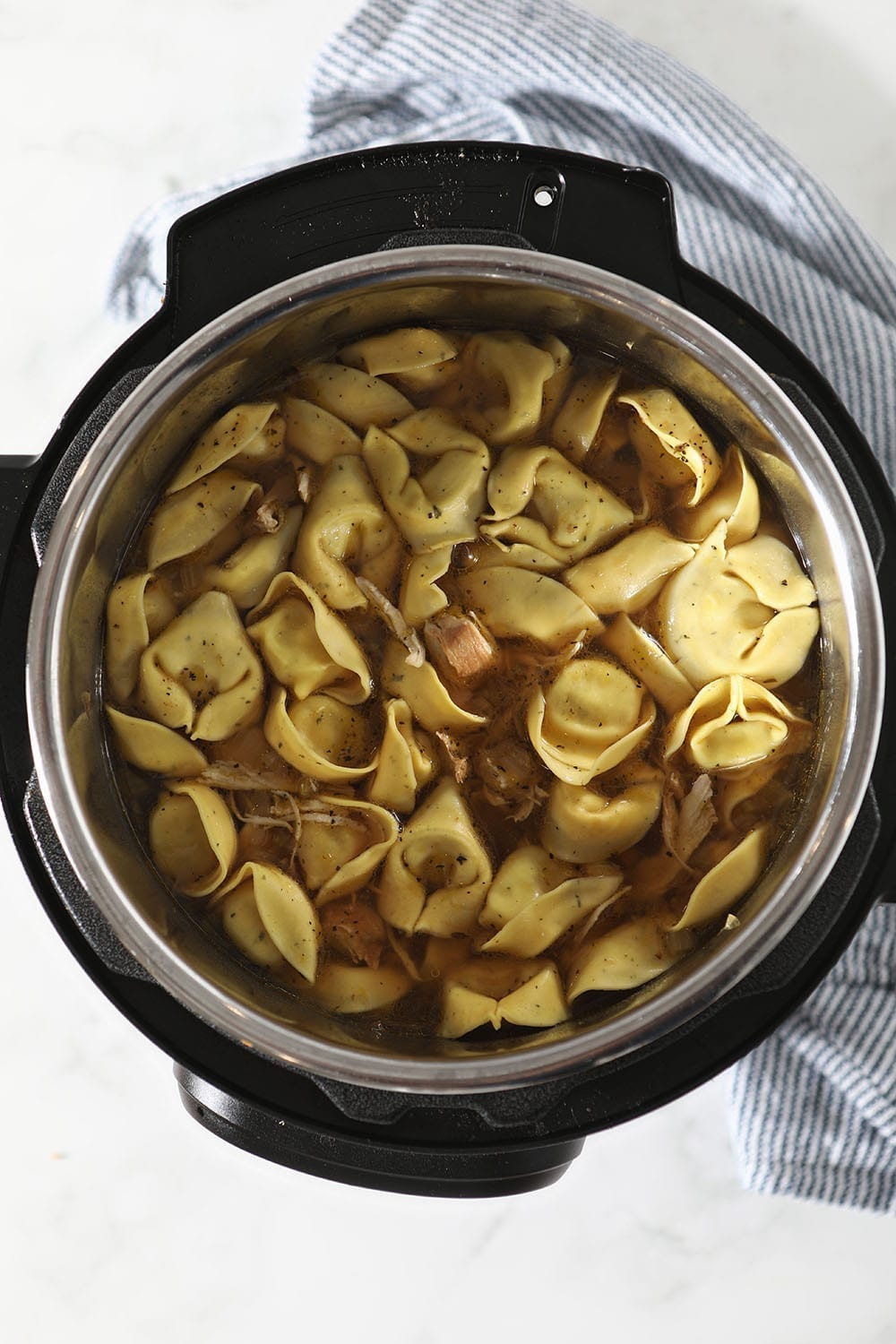 Tortellini is added to the slow cooker, from above