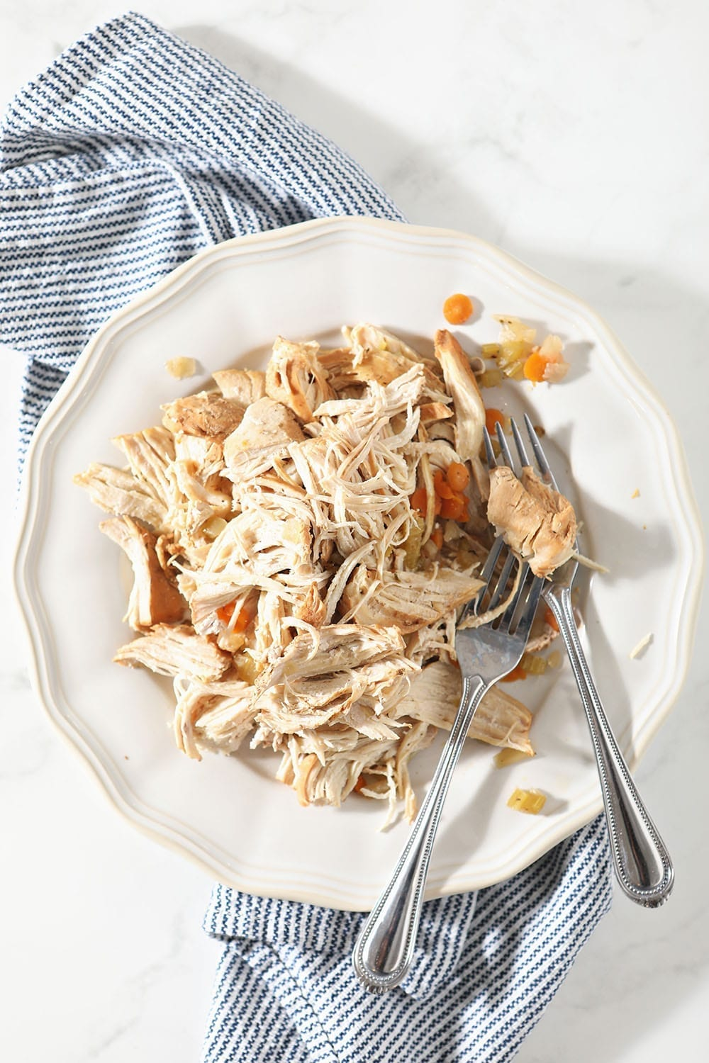 Shredded chicken is shown on a white plate with forks