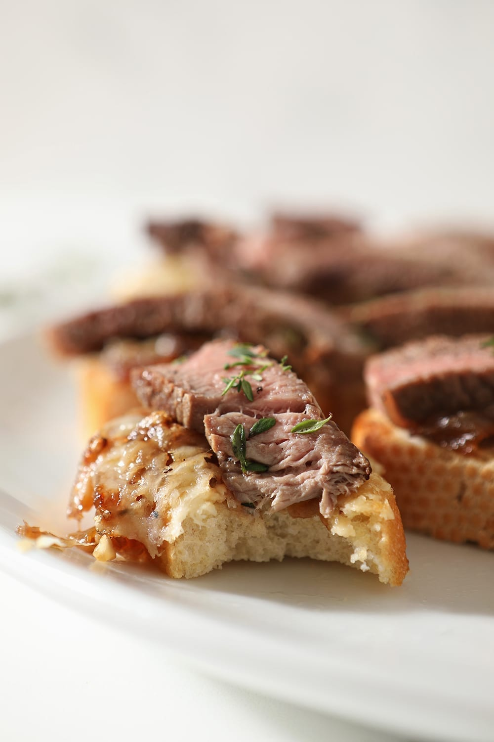 Close up of a bitten into Steak Bruschetta on a white platter with other bruschetta