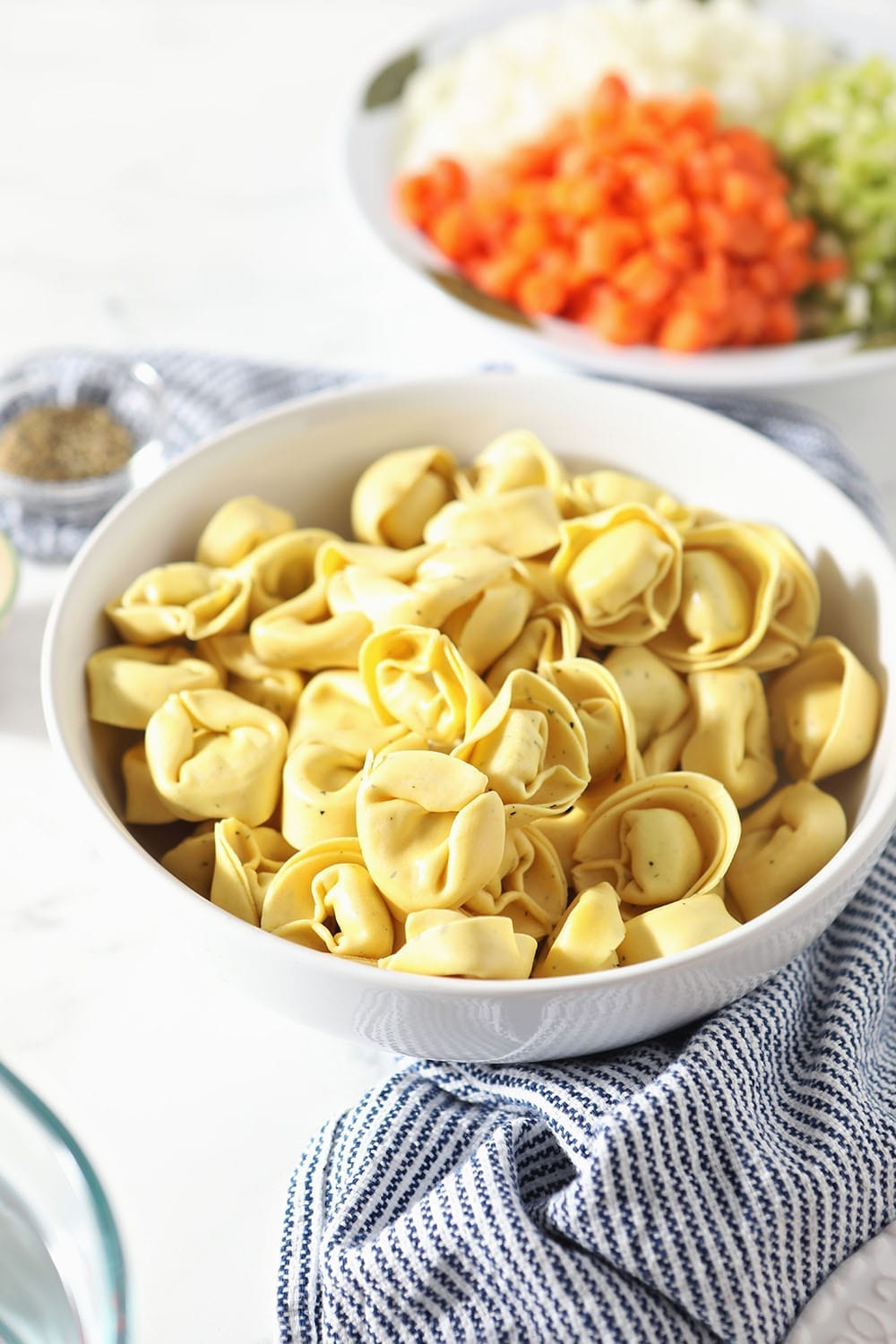 A bowl of cheese tortellini sits on a striped blue towel
