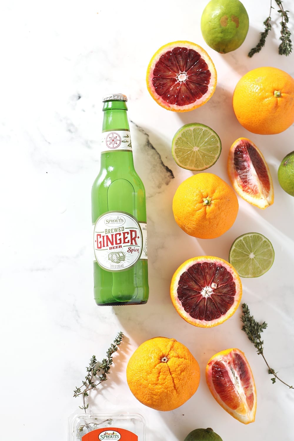 A ginger beer is surrounded by blood oranges, limes and fresh thyme on a marble background