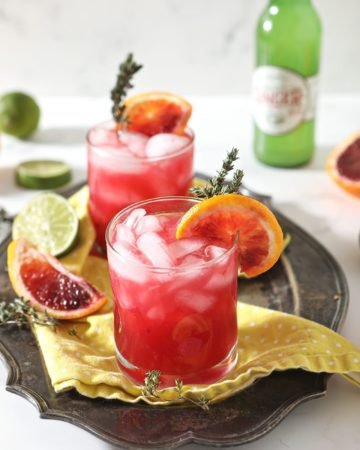 Two Blood Orange Mocktail Mules sit on a yellow napkin on a silver platter, surrounded by sliced citrus