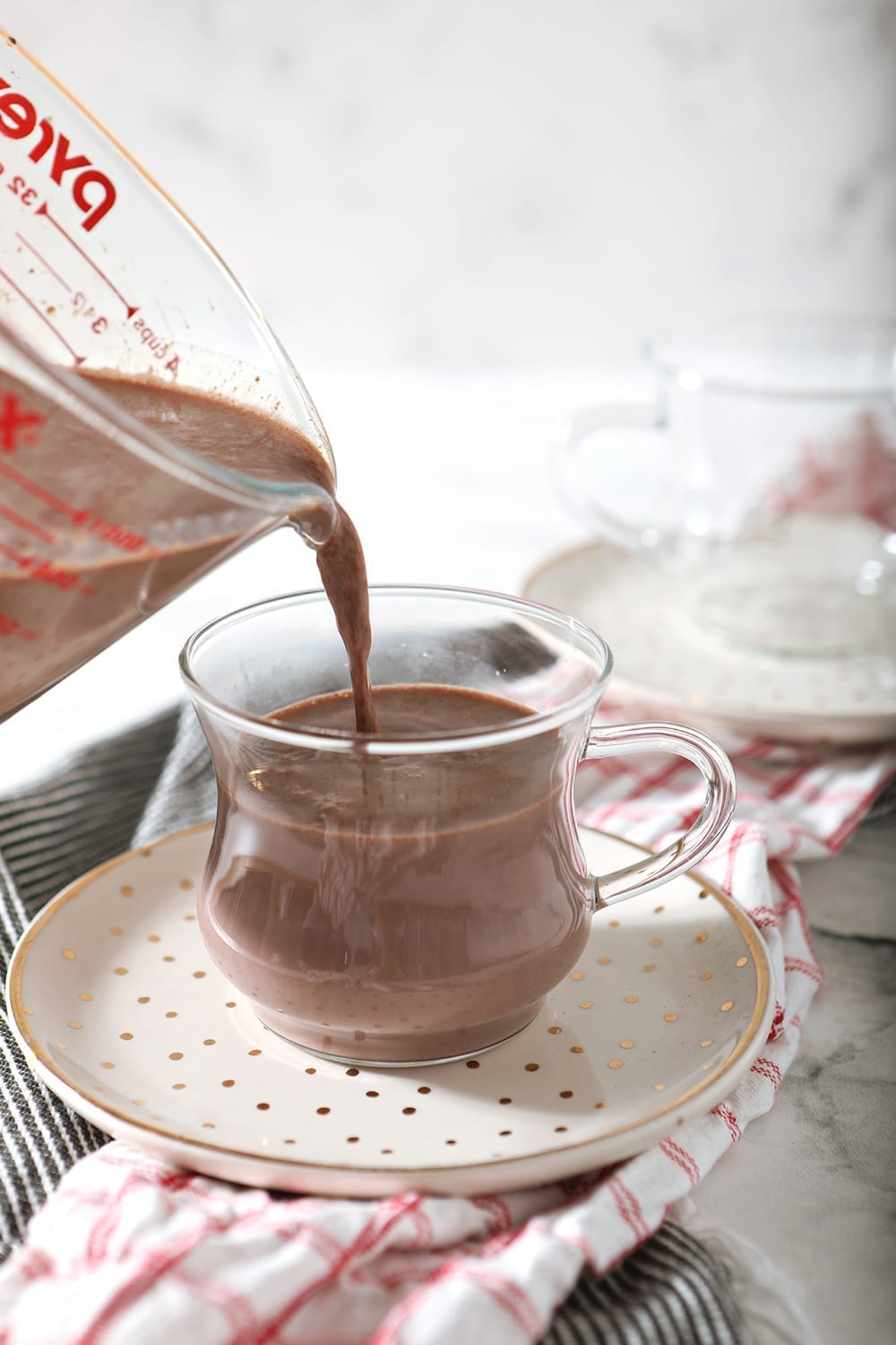 Gourmet Hot Chocolate is poured into a clear mug on a golden polka dot plate