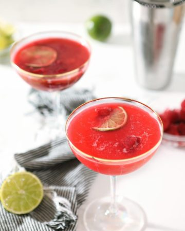 Two glasses of Raspberry Moscow Mules sit on a marble countertop, with a shaker and limes