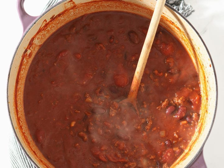 A Dutch oven is shown from above holding a ton of Shiner Bock Beer Chili