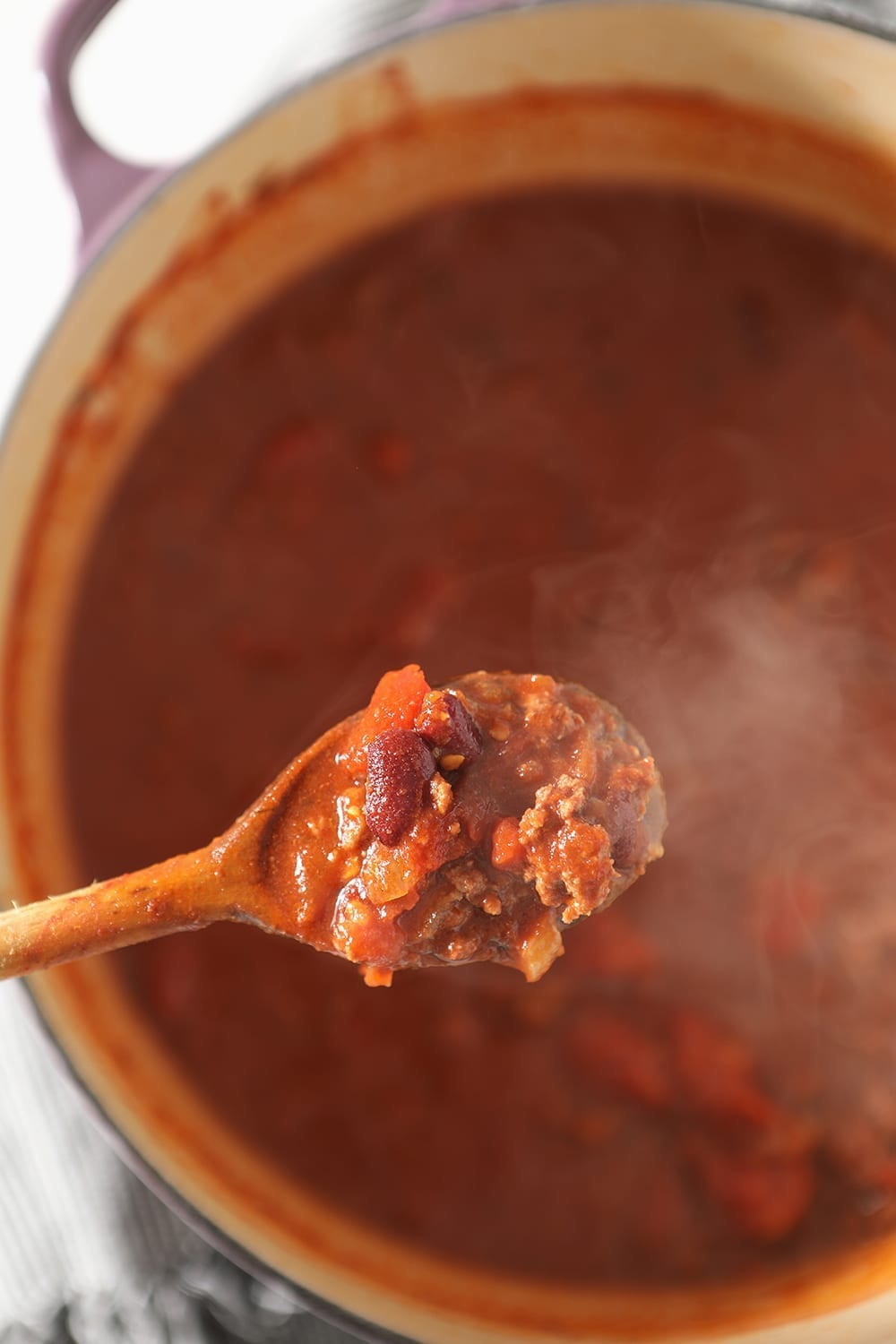 A wooden spoon lifts Beer Chili out of the Dutch oven, from above