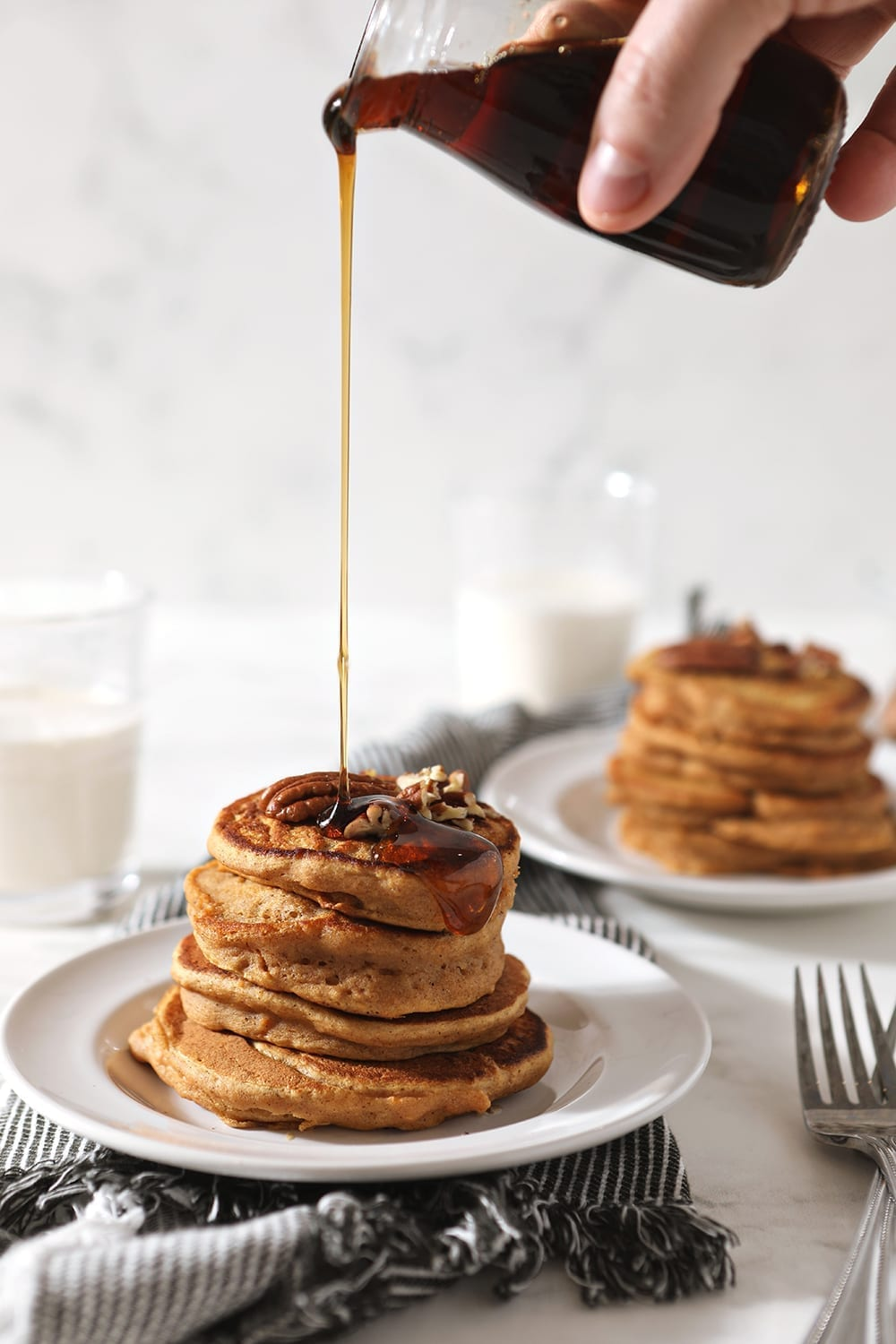 Maple syrup is drizzled onto a stack of Sweet Potato Pancakes