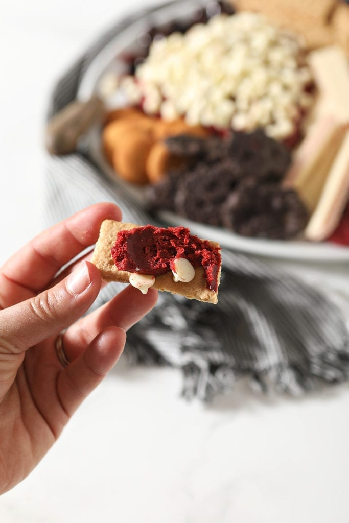 The red velvet cheese ball is smeared on a piece of Graham cracker, before consuming