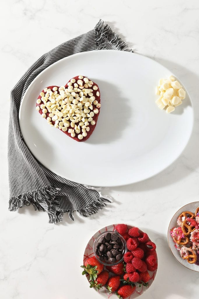 A heart-shaped dessert cheese ball sits on a white platter with cheese rounds