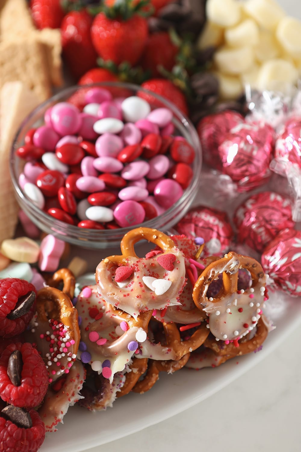 Close up of pink and white ingredients, including candies, white chocolate pretzels and more, on the platter