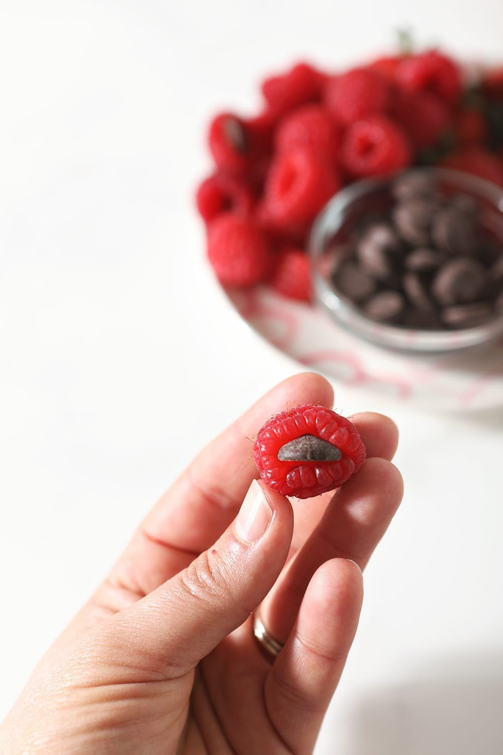 A person holds a raspberry, stuffed with a dark chocolate chip