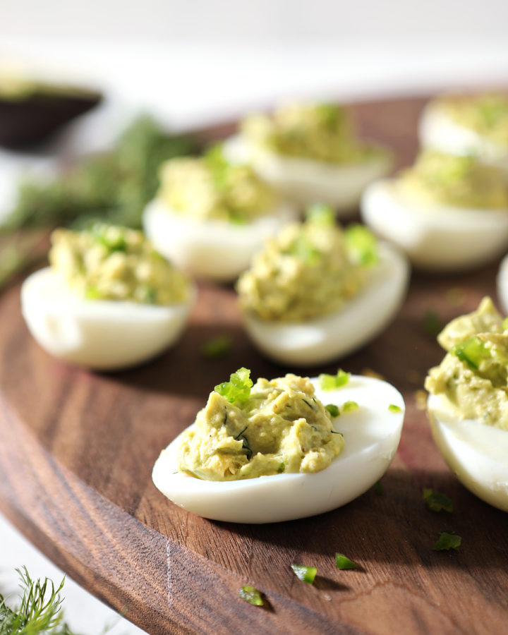 Avocado Deviled Eggs are served on a walnut board, from the side