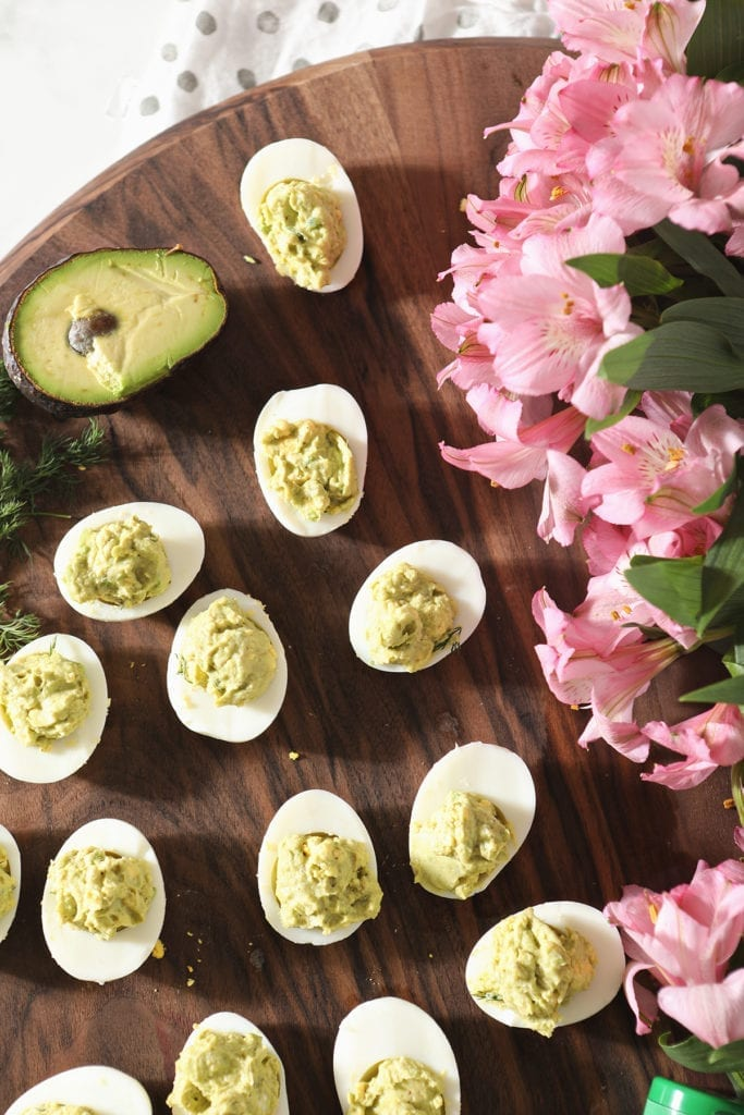 Overhead of avocado deviled eggs with pink flowers and avocados as decoration