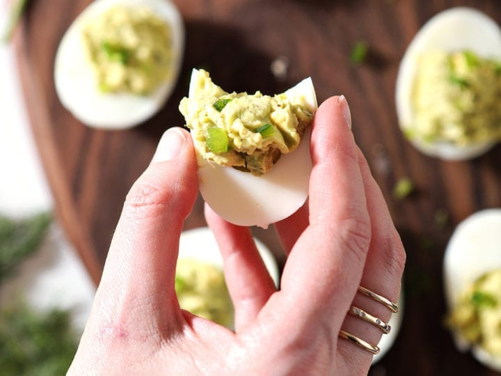 A woman holds a half-bitten deviled egg, from above