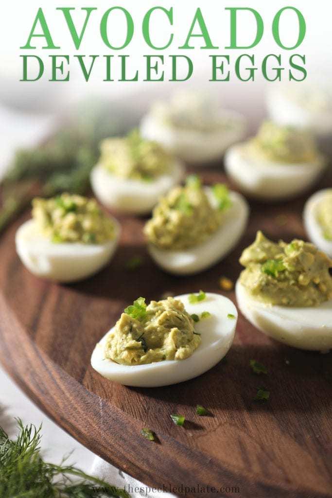 Avocado Deviled Eggs on a wood platter, with Pinterest text