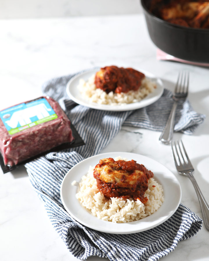 Two plates holding Enchilada Meatballs, served over rice, are shown on a striped blue towel