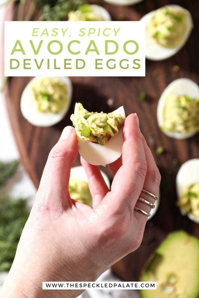 Overhead of a woman holding a deviled egg over a platter with Pinterest text