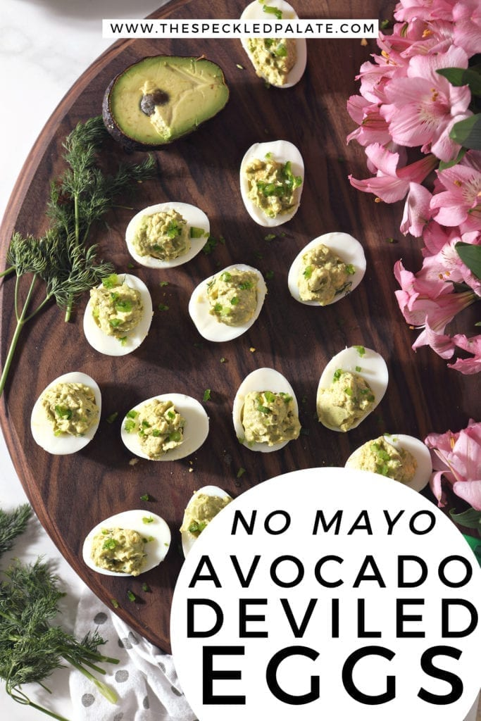 Overhead of avocado deviled eggs on a wooden board with pink flowers and Pinterest text