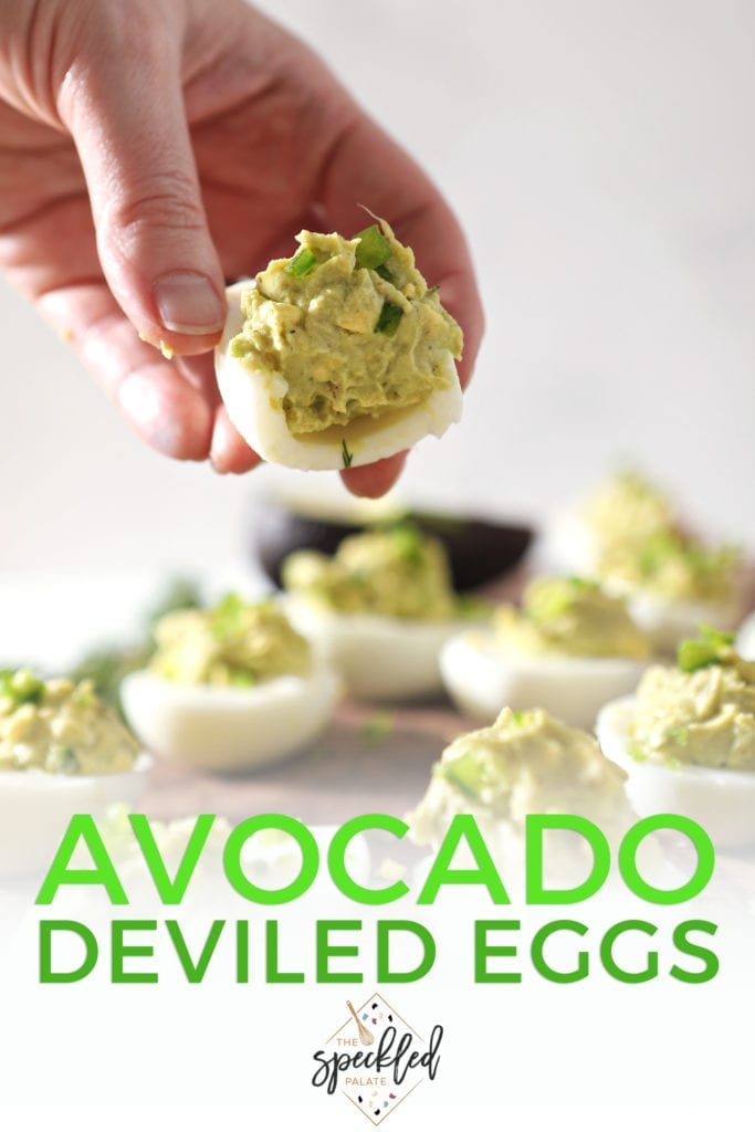 A woman holds a half-eaten Avocado Deviled Egg, with Pinterest text