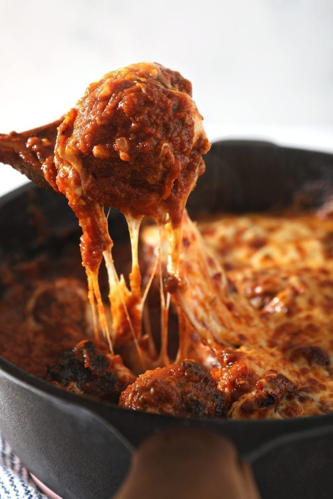 A wooden spoon pulls a meatball out of the skillet, with a cheese pull